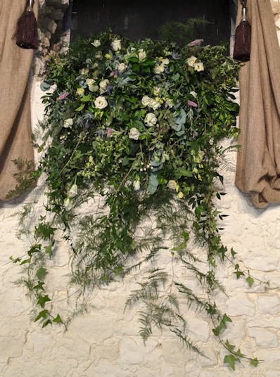 Foam free floral installation for a wedding. Foliage trailing from a window ledge.