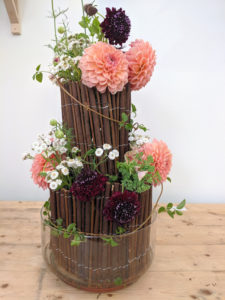 Summer flower arrangement, two layers of rolled sticks, within a glass basin.